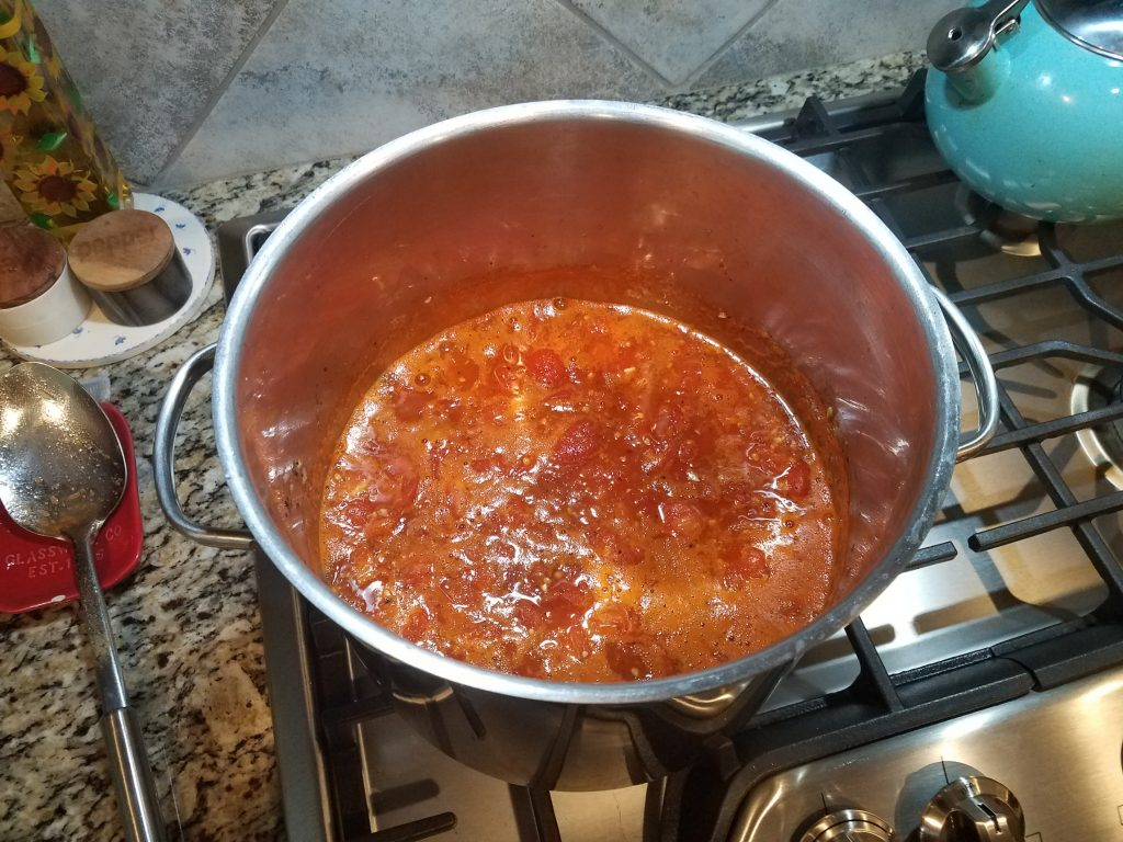 Sauce in stainless steel stockpot simmering.